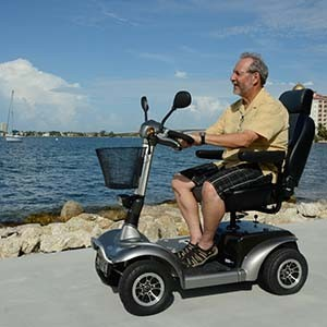 A man riiding his mobility scooter by the beach