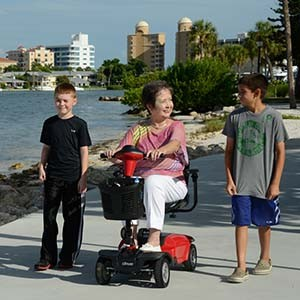 Woman on a mobility scooter with two boys walking along