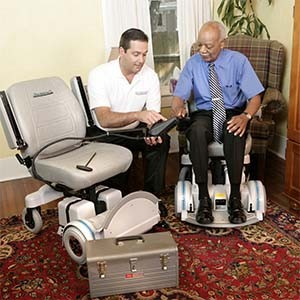 Hoveround technician helping an elderly man with his Hoverouns