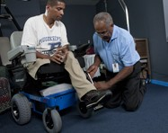 A Hoveround technician helps adjust a Hoveround power wheelchair